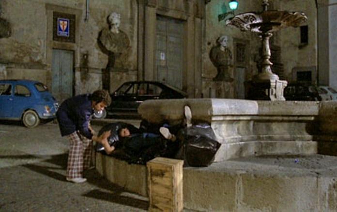 """Scena del film """"Bianco, rosso e Verdone"""", ambientata in Piazza Umberto I, a Bassano Romano. In primo piano la fontana, sullo sfondo Villa Giustiniani."""