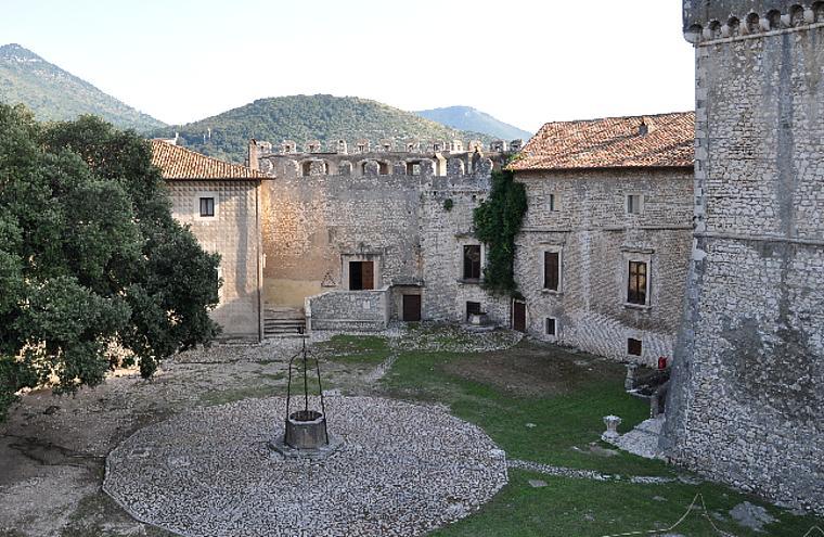 Castello di Sermoneta, vista parziale del Mastio e dell'edificio della Sala dei Baroni, dalla Piazza d'Armi. Al centro della Piazza d'Armi, la cisterna.